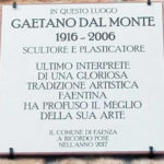 Targa in via Sarti 3 posta nei pressi di quella che fu la sua bottega in cui presero vita quelle opere che hanno reso Tano Dal Monte tra i più preziosi testimoni della tradizione artistica manfreda.